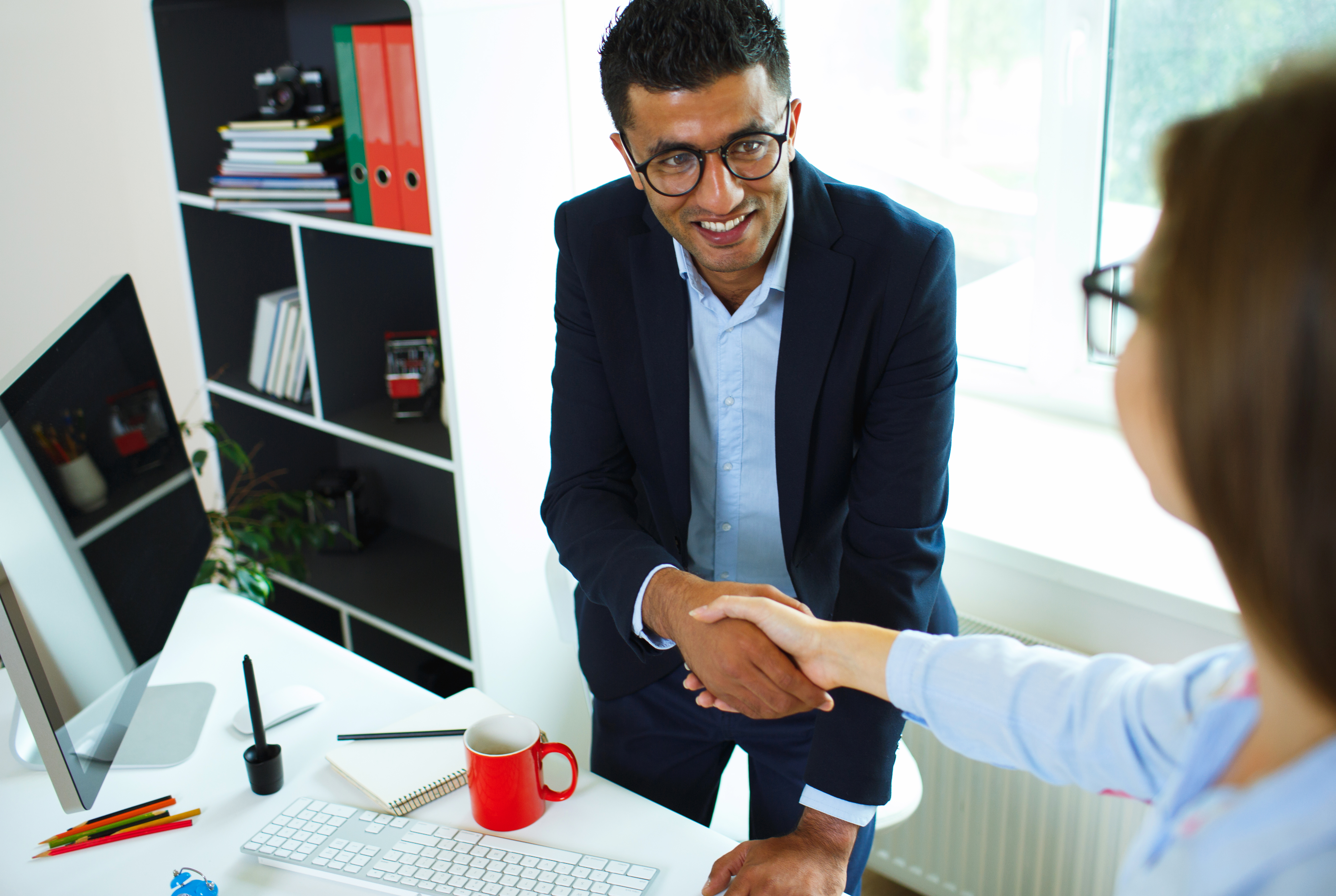Young businessman and woman shaking hands in office